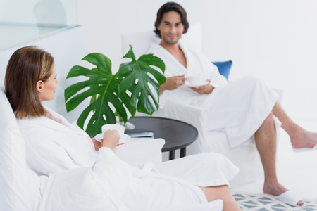 Rear view of woman sitting in chair and talking to handsome man while drinking tea