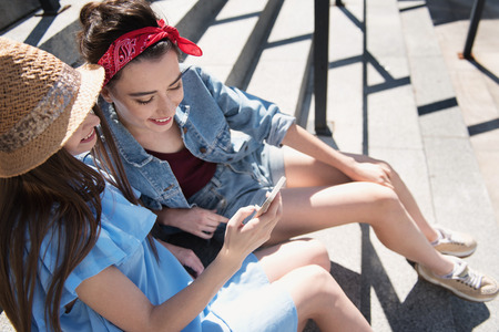 stroll: pretty women smiling and looking into a smartphone Stock Photo