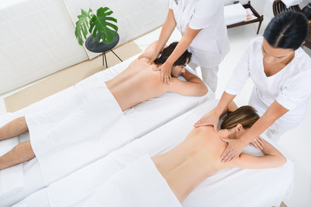 Top view of adult couple receiving back massage while on holiday at beauty spa