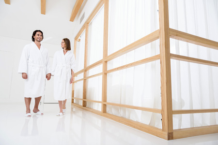 holding hands while walking: No stress today. Beautiful couple wearing in white terry robes and holding hands while walking along hall of spa center