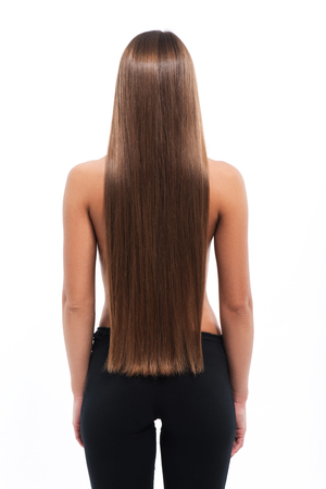 Young woman is standing and showing her long smooth straight brown hair. Isolated