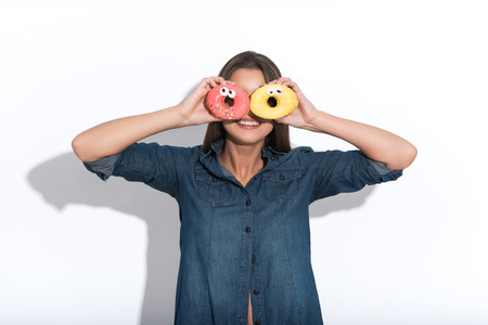covering eyes: Joyful young woman is covering eyes with donuts. She is standing and laughing. Isolated