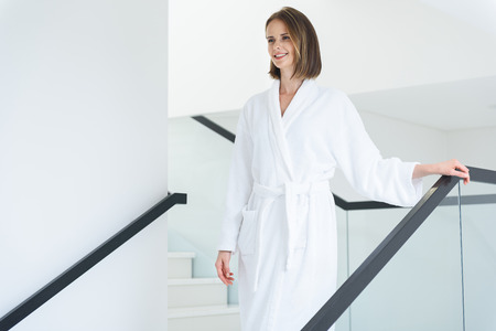 cropped shot: Cropped shot of pretty brunette woman wearing white bathrobe and coming down stairs in hotel spa