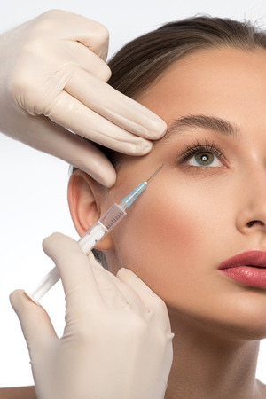 cosmetologist: Professional cosmetologist is making botox injection into female eye area. Isolated Stock Photo