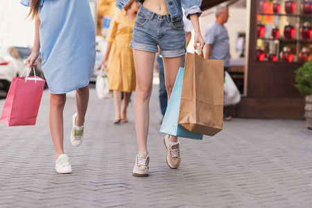 waist down: shopping concept, waist down view of a girl holding bags in their hands
