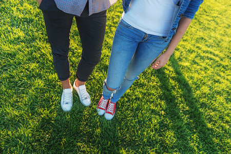 waist down: waist down view of couple on the green grass with copy space