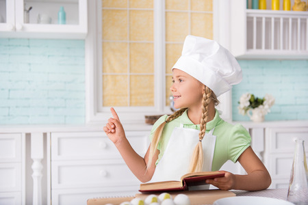 I have a great idea. Pensive girl is preparing for cooking. She is holding cookbook and pointing finger up. Child is standing near table in kitchen and laughing Banco de Imagens