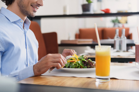 Taking break in cafe. Cropped shot of businessman having lunch in cafe, sitting at table and eating salad, holding cutlery in hands Stock Photo