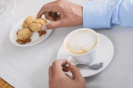 Delícia de cappuccino. Tiro recortado, de, homem, segurando, xícara café, e, biscoitos, outro, mão Foto de archivo