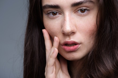 beauty and skincare concept, portrait of a calm peaceful freckled brunette looking into camera Stock Photo
