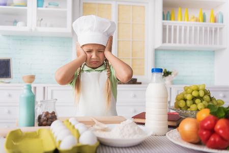 decepci�n: La ni�a tiene miedo de la cocina. Ella cerr� los ojos con la decepci�n y el llanto. Ni�o est� de pie en la cocina y tocar su cabeza