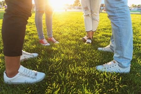 waist down: waist down, friends standing on the green grass
