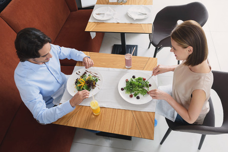 restuarant: Sharing healthy lifestyle. Top view of happy smiling couple having lunch together at restuarant while eating salad
