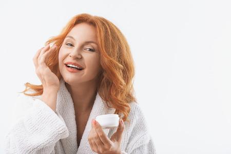 Blije vrouw van middelbare leeftijd is de toepassing van crème op haar gezicht. Ze is op zoek naar de camera met geluk en glimlachen. Vrouw staat in witte badjas. Geïsoleerd en kopie ruimte in rechterzijde