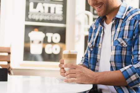 Enjoying his coffee break. Cropped photo of smiling young man sitting at street side cafe and enjoying latte Stock Photo