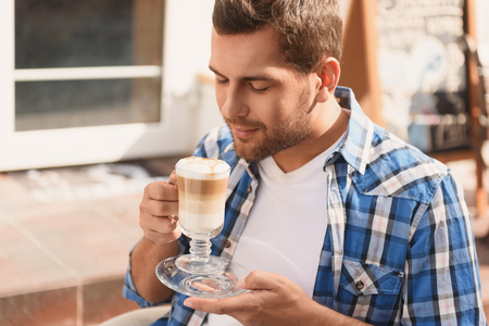 Coffee makes his day. Attractive man enjoying aroma of his latte while sitting at street side cafe