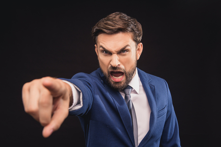 exacting: You. Irritated businessman is shouting at someone with aggression. He is standing and pointing finger forward. Isolated