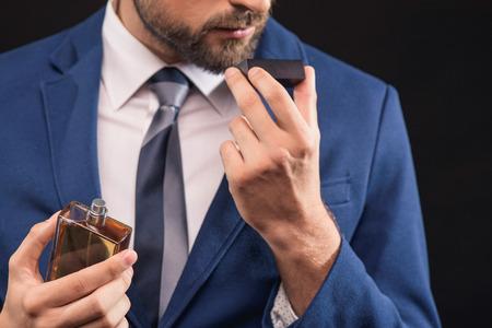 자신감이 젊은 사업가 남성 향수의 향기를 즐기고있다. 그는 서 있고 병을 들고. 외딴