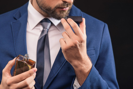 Self-confident young businessman is enjoying smell of masculine perfume. He is standing and holding bottle. Isolated