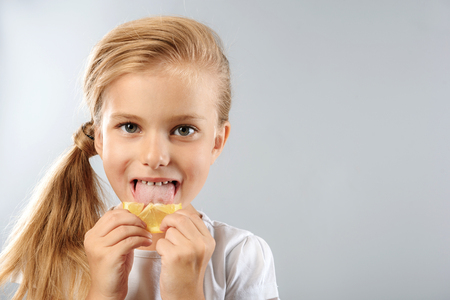 prophylaxis and health care concept, close up of funny child licking sour lemon Stock Photo