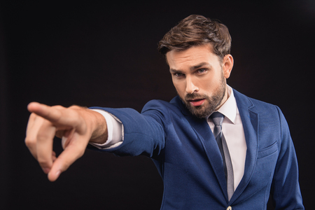 exacting: Hey you. Serious young businessman is pointing finger forward with authority. Isolated on black background