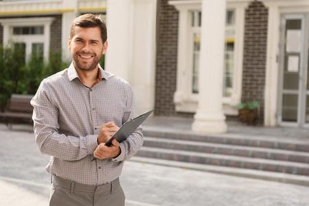 Echte professional. Portret van mannelijke makelaar in onroerend goed staande buiten woningen, klembord en glimlachen te houden