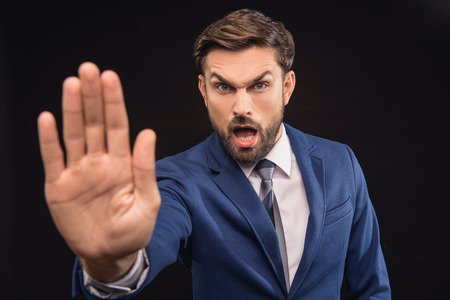 exacting: Stop. Angry male boss is stretching arm forward and shouting. Man is standing and looking at camera with irritation. Isolated