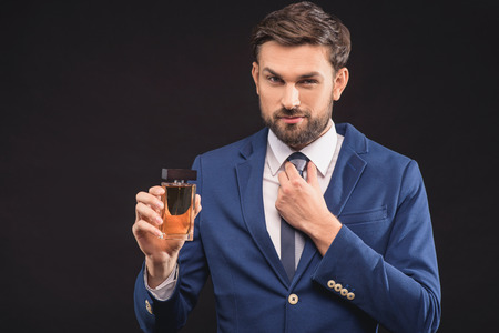 Attractive young businessman is presenting bottle of masculine perfume. She is adjusting tie and looking at camera with confidence. Man is standing in suit. Isolated