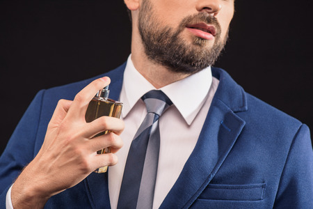 masculine: Sexy young man is perfuming himself with masculine cologne. She is standing and posing in suit with confidence. Isolated