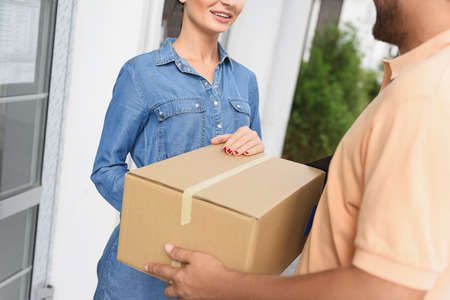 cropped out: Carrying out urgent delivery. Cropped shot of smiling woman hands accepting delivery of box from deliveryman