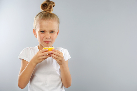 prophylaxis: prophylaxis and health care concept, little girl tastes sour lemon