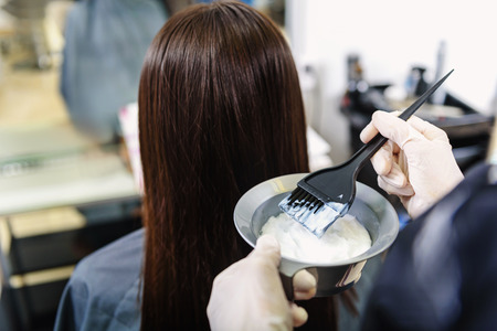 stylist holding brush and hair conditioner in front of a hair