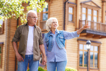 Joyful old married couple are enjoying walk and smiling. They are holding hands. Woman is pointing finger sideways and smiling Stock Photo