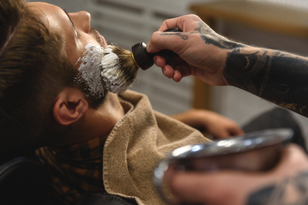 shaving cream: hairdresser applying shaving cream on face of man, concept of shaving