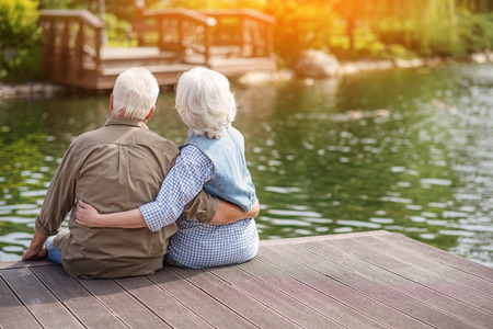 Loving old couple is watching the sunset in park with enjoyment. They are sitting near lake and hugging