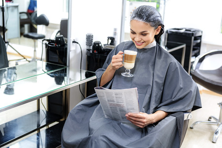 barbershop: young woman reading and drinking in barbershop Stock Photo