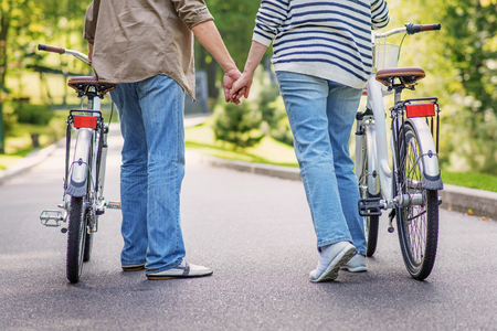 Close up of legs of old man and woman riding bicycles on road in park. They are holding hands with love