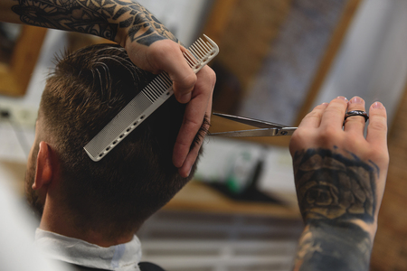 barber holding and cutting hair of a client, haircare concept