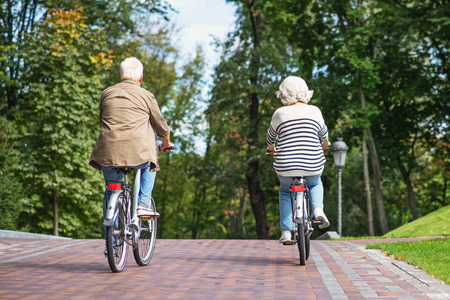 Mature man and woman are enjoying ride by bicycles in nature. Focus on their back