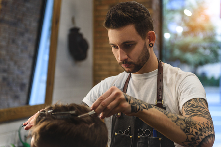 face of concentrated barber with hair cutter, haircare concept