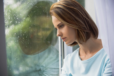 young beautiful lady looking out the window, autumn blues concept Stock Photo