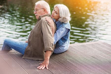 pareja casada madura está sentado al lado del lago y relajante. Ellos están abrazando y sonriendo