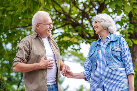 gentleness: Happy old couple is enjoying walk in park. They are holding hands and looking at each other with gentleness