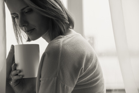 lonesome: beautiful woman holding beverage with copy space, black and white Stock Photo