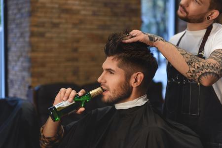 ハンサムなひげを生やした男性ヘアスタイリスト作業しながらビールの瓶でリラックス