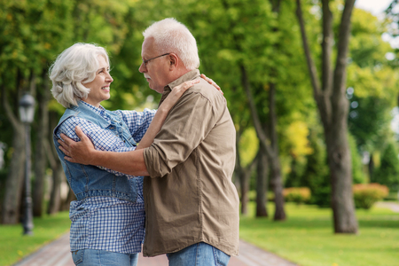 Happy old married couple is embracing and smiling. They are standing on alley in park Stock Photo