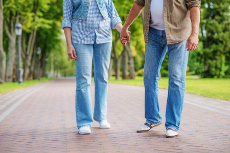 stroll: Close up of old married couple legs walking on alley in park. They are holding hands with gentleness