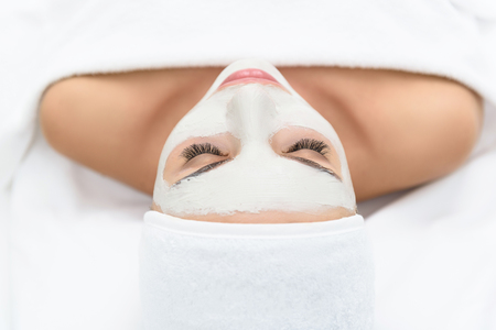 Pretty girl is relaxing with facial cream mask. She is lying at spa with enjoyment