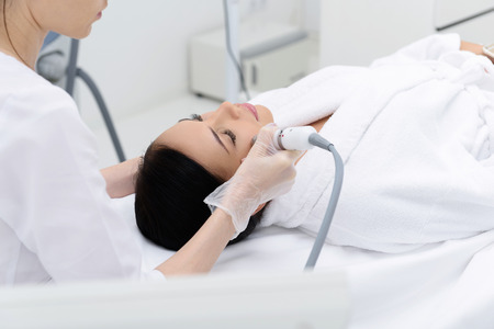 Relaxed young woman is getting cavitation facial massage by cosmetologist. She is lying on table. Her eyes are closed with enjoyment