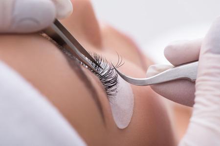 Cerca de las manos de esteticista pegando la pestaña artificial a ojo femenino Foto de archivo